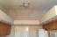 Vaulted-ceiling in kitchen with plant-shelves and can lights