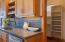 New metallic tile backsplash with under counter lighting. Entry to large walk in pantry.