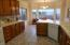 Kitchen view of Mountain and Backyard, Neutral Counter Tops, Tile Floors and Oak Cabinetry