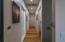 Hallway in master bathroom leading to walk-in shower, walk-in bathroom, and single car garage.