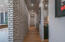 Hallway leading to upstairs bathroom, laundry room, stairs to walkout basement, and two car garage.