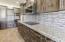 Digital cooktop, double ovens and glass tile back splash.