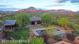 Be embraced by beauty and serenity in this exquisite, warm, and inspiring contemporary masterpiece, an extraordinarily beautiful home set upon a secluded hilltop on 1.73 acres bordering U.S. Forest Service land in West Sedona. It has incredible red rock view panoramas from its private and serene setting, capturing unblockable views of Thunder Mountain, Coffee Pot, Cathedral Rock from the backyard pool area, the entire eastern red rock rim including Wilson Mountain and Giant's Thumb, and much more. A soothing waterfall and pond welcome you home as you draw near to the entry. Stepping into the light foyer, you sense that this is no ordinary home. Be sure to see the 3-D Self Guided Tour in Photos. (See additional details in Supplement).