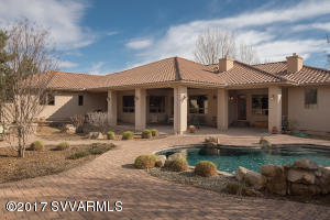 Indoor and Outdoor living at its finest, located in the heart of Camp Verde in the center of Az. Beautiful custom Home has it all, 4 beds all with private baths, all have travertine tile floors, shower/tubs and solid travertine counter tops. Two of the bedrooms have private courtyards, master has fountain water feature. Upgraded Alder cabinets throughout. Kitchen with commercial grade appliances, pot filler, granite counters, island with prep sink adjoins wetbar and dining for added and open area. Custom wood Lowen Windows add warmth along with solid Alder doors, alder trim and Brazilian cherry hard wood floors. Privacy on back covered patio, pool, waterfall, built in BBQ/kitchen, open sitting area and fireplace, pool bath conveniently attached.  All of this luxury sits on over 2 irrigated