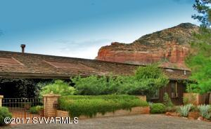 One of a kind, classic Sedona styled home on 9.7 acres in town. Don Woods design, saltillo tile in main living areas with huge living, dining, family rooms, library, separate elegant guest suite. Enjoy panoramic views from the large deck that wraps around to pool area.  Master suite is fantastic with his & hers closets, huge dressing area, a refreshment center, exercise room.  Greenhouse, dog run. Horses allowed.
