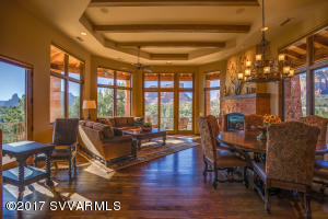 Great Room featuring wood beamed ceilings, wood encased picture windows, and stacked stone fireplace.