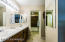 Master bath with walk-in closet to right and tub/shower in the back