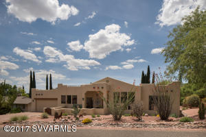 Stunning front view of Hacienda with lovely desert scape spotlighting ocotillo and other cactus and blooming plants.