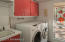 Spacious laundry room with window, upper and lower cabinetry, front loader washer and dryer, sink, main level