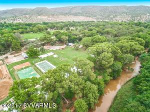 Ranch on Oak Creek near Sedona. Equestrians can ride on F. S. LAND. Ideal for a Family Estate or small horse ranch. Ten structures and improvements: a 4000+ Sq. Ft. administration building that could be turned into an amazing residence or other uses. Cabins and mobile homes used for residential or students dormitories and classrooms, library, science lab. Great horse training facilities with tack rooms and riding arena. Large pool multiple wells and grandfathered irrigation water. Enjoy full basketball and tennis courts, volleyball and skateboard park with outdoor lighting. Hiking and horseback riding on U.S. forest Service lands nearby