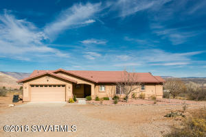 You will love the views from this custom built home. Solid 2x6 construction with fire sprinklers. The open split floor plan is inviting and you will love the back deck to enjoy the panoramic views all the way to Sedona. Custom built cabinets in the kitchen with good counter space & vaulted ceiling compliment this great room. The master bedroom is oversized with large walk-in closet, dual sinks and step in shower. The office is located just off the master for privacy & has private entrance to back low maintenance deck. All tile thru out main living area, carpet in the bedrooms. Drip system around the property. Oversized garage has built in workbench. Side patio is perfect for you hot tub & has 220 breaker for convenience.