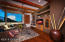 Charming and Cozy this Media Room has hand scraped wood flooring, rustic ceiling beams, a wet bar, fireplace and corner window views of Wildhorse Mesas and the enclosed Courtyard.A custom carved ceiling fan adds to the charm.