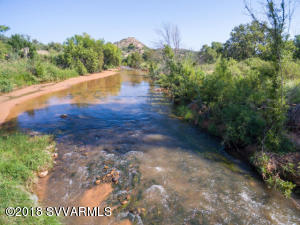 This premier property at Sexton Ranch offers serenity, luxury living, extraordinary value, and quick access to the best of the Verde Valley. Five peaceful acres with Oak Creek frontage, bordering National Forest, and ample room for organic gardening, pets, and even your own vineyard. This luxurious 3,400+ Sq|Ft home has been completely remodeled inside and out with high-end finishes, the latest systems, and access to high-speed internet (a rarity with country living). Grandfathered water rights, creek frontage, a private gated road, and plenty of room for expansion to add a guest house, barn, or ramada to watch the sunsets. A detached red barn for plenty of toys, and a charming cold cellar for the connoisseur who dreams of having an authentic room for the wine collection...
