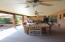 Extended covered back patio with ceiling fans and shades.