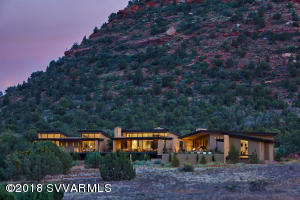 This stunning desert contemporary home sits harmoniously on its 4.65-acre site backing to pristine National Forest land, capturing the incomparable red rock vistas and mountain views within the beautiful and prestigious Aerie community in west Sedona. Combining stunning architecture, a fully single-level floorplan that flows seamlessly from end to end, heightened attention to every exquisite detail,and majestic panoramic views, this is a true world-class residence on a level all its own in Sedona.The long, gated private driveway brings you up to the elegant entry with beautiful desert landscaping. A soulful sense of privacy against the National Forest blends into the expressively inclusive nature of the home and its welcoming spirit as you approach the front entry. (see more)