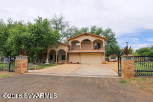 Beautiful Custom Home in serene setting of Camp Verde's green belt along the Verde River. Almost two acres on irrigated double lot with room for two horses. Fully landscaped with pecan trees, various fruit trees, award winning irises & grass. Most of the property is perimeter fenced & cross fenced.Nice view of the Verde River from your private master suite balcony.  Owner is a retired home builder who built this for himself with only the highest quality material & workmanship in mind. 2005 construction the County considers 1975 due to original slab/walls. All new top of the line electrical & plumbing throughout. Solar water heater. Surround sound in both living room & master bedroom. Entire house speaker system. RV dump & separate 50 amp meter. Custom solar powered front entry gate.