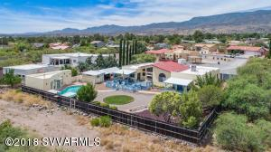 UNBELIEVABLE AIR B&B POTENTIAL! 4 BEDROOMS WITH A POSSIBLE 5TH.  3BEDROOMS HAVE THEIR OWN ENTRANCE! KITCHEN W/GRANITE COUNTERS.  FULL GUEST HOUSE WITH BATH AND PARTIAL KITCHEN, POOL AND BEAUTIFULLY LANDSCAPED YARD WITH PANORAMIC VIEWS OF MINGUS AND SEDONA RED ROCKS!  RV PARKING AND CARPORT, PLUS SHOP ALL ON 1/2 ACRE.      Huge 22 x 17 room off the garage - could be used as office (already has built-ins) or as in-law quarters.  Main house kitchen has center isle & granite counters! This house boasts decks from master bdrm & 2nd bdrm, also living rm & kitchen. All w/knockout views of Red Rocks.  Property has a workshop w/adjoining carport.  All this on over 1/2 acre!  Heating & cooling on right side of house runs on a Hydronic system (water). The left side is heated/cooled by gas