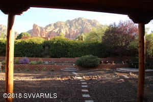 The best of all worlds in a quiet, view wrapped, area of Sedona known as Pine Valley. Discover this ''off the beaten path'' neighborhood- no tourism or commercial activities. Thrilling views of red rock mountains! This large parcel is graced with a modern Santa Fe style home with a split floor plan. The enclosed & private back yard is immense with multiple areas to enjoy from the gazebo to the terraced birding refuge to shaded patios. The interior is drenched with natural light from large windows in a home beautifully oriented for seasonal advantage of shade in summer & sunny warmth in the summer. Open floor plan with a big family room off the entry/living area. Spacious master suite with patio access. Guest bedroom also enjoys red rock views & patio. Peace & serenity can be yours!
