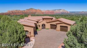 Located on the Sedona Golf Resort, this classic Mediterranean residence consists of 3 bedrooms, 3.5 baths, a study with its own entrance, situated on 1.1 ac with panoramic red rock views. This highly appointed custom home has floor-to-ceiling estate pocket doors and over-sized windows that lead to a spacious outdoor terrace. The outdoor patios have scrolled wrought ironed railing, porcelain tile, fire pits and a waterfall feature making it ideal for outdoor entertaining. Escape to the elevated star gazing deck to enjoy sun-kissed sunsets and shooting stars! Flawless finishes unfold to include Quartzsite, Onyx, Granite, Petrified Wood and Tumbled Travertine tile. The lot to the east of the home is included in this sale. Please refer to the Supplement for a list of upgrades.