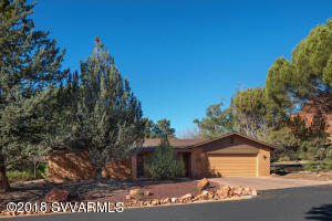 This West Sedona home has been lovingly maintained, and offers an ideal single-level floor plan sitting on a desirable corner lot. It is Move-In Ready with generous room sizes and an open floor plan, with a wonderful brick fireplace in the spacious Great Room and skylight overhead, right next to the spacious Arizona room with built-in book shelves and storage, both with lots of natural light. The kitchen and adjacent laundry room provide plenty of cabinet storage. The living room has a peak-a-boo view of Coffee Pot. The ample back porch area and large enclosed Arizona Room overlook the backyard, with a short walk to the National Forest.