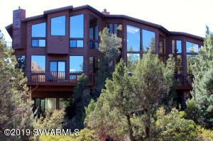This spacious home is in a breathtaking setting surrounded by the amazing red rock formations that are Sedona. Situated with it's back to the Coconino National Forest the large picture windows in this lovely home gives you the feeling of serenity, elegance, and seclusion. This home with it's beautiful red wood siding, features dramatic high ceilings and decks run it's length. The indoor pool, jacuzzi, two steam units and two saunas will make this home your personal relaxation retreat. When life creeps in, there is a separate washer/ dryer located near the pool and a laundry shoot from the master bedroom to the first floor laundry room which makes laundry a breeze.