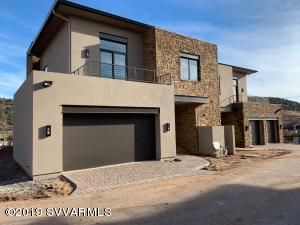 Enclave 1 exterior showing natural stone facade and paver driveway