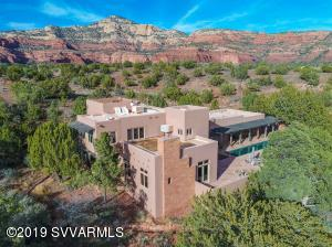 Experience breathtaking 360 degree views from the rooftop deck of this elegantly appointed 3900+ sq ft home on 8.47 acres bordering National Forest land and nestled in the arms of Bear Mountain in the Red Rocks of Sedona.  Imagine yourself under the best shower in the world outside the master suite with views of Bear Mountain, Doe Mountain, Cathedral and Courthouse! Walk on the flagstone floors radiantly heated in winter; touch the stacked stone, exposed wood beams, hand troweled Venetian plaster walls with radius corners and elegant English slate counter tops that define the kitchen, living and dining rooms. Stroll along the entry colonnade overlooking the outdoor pool, waterfall and spa. The 2 guest bedrooms with baths open onto this patio