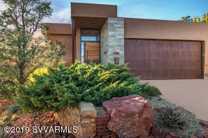 The exterior of this property is stucco and stone with rusted metal fascias and matching garage door. The house is surrounded by mature vegetation and has a built in red rock water feature..