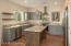 A spacious kitchen--with granite counters and an island accommodating two stools--offers views from wherever you stand.