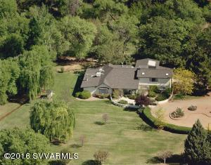 Four ''Green Acres'' of tree filled & irrigated riparian property with a bright & open 3431 Sq. Ft. (4 bd 2 3/4 ba home). High ceiling's & scenic views from the huge windows. Large artist's studio full of skylights & home has two fireplaces. River fed ditch water from Oak Creek irrigates & flows through the land and pond. Grandfathered surface & well water irrigation rights. Lushly landscaped w/ fruit trees,huge willow & cottonwood trees. Secluded -Quiet & Very Private location. Great soil for gardening & pastures for your horses & farm animals. 2 car attached garage with workshop. Greenhouse & separate Barn (or 2nd garage). Mother-in-law set up quarters. No H.O.A or C.C.R.'s - No Fees. Private entry gate and totally fenced.  Currently good B&B income and prev approved for assisted living.