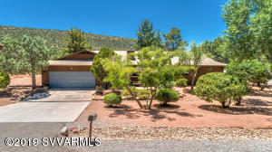 Quintessential  Ranch Rambler nestled amongst enveloping trees in the Pulse of West Sedona.  Lots of Room to Expand on this generous 1/3 acre.  Home boasts 3 good sized bedrooms with another room that could be an office? Art Studio? or a 4th bedroom. 2 Covered outdoor decks  to enjoy the outdoors without the blazing heat!  Kitchen Remodeled with pull out cabinets, corian counters and 2 pantries.   Over Sized 2 Car Garage for cars and toys. Best of both worlds being close to  the hustle of  West Sedona AND the  Associations Open Space for fido or evening strolls.  Various improvements over the years by the owners and  City Sewer, AZ Water and Natural Gas make this an opportunity!