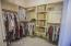 Large walk in carpeted closet with built-ins.