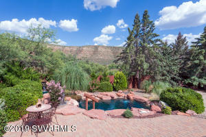 This beautiful sanctuary in Sedona is one-of-a-kind, situated on nearly a 1/2 acre, and remodeled with over $300,000 in upgraded amenities inside and out! Upgrades include a custom new 4-car garage with a work bench area, bathroom + shower, an abundance of  storage. Stunning new French oak flooring throughout; new high-efficiency HVAC system (2019) + 2 air purifiers (great for allergies), landscaping; new upscale pavered driveway +matching pavers in the backyard; new kitchen appliances; new water filtration system in the lagoon pool, new split AC unit in master  and many more upgrades! This beautiful oasis is nestled in the serene area of Pine Valley, Sedona, with  beautiful red rock hiking trails nearby, and miles of national forest. No homeowner association dues or restrictions..