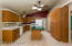 Kitchen with custom built storage cabinet and wine rack. Ceiling fans.