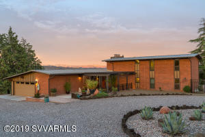 Midcentury modern oasis in the center of historic Clarkdale. This gem sits on just over 1.5 acres w/ both east & west panoramic views.Totally renovated 4 bedroom, 3 baths w/ 3 outdoor seating areas w/ 2 water features. The centerpiece of this home is a floor to ceiling black lava rock wall w/ two fireplaces. Original copper detail on one side & intricate pottery shard mosaic on the other create a spectacular focal point. Stunning architectural steel & wood staircase to the loft, bedrooms & full bath affords a dramatic open view of the kitchen, family room & Mingus Mtn view. Main living on the first level with generous master suite at one end & second large bedroom with room-sized walk in closet on the other. Walls of glass in the living room open to a Red Rock panorama. Supplement.