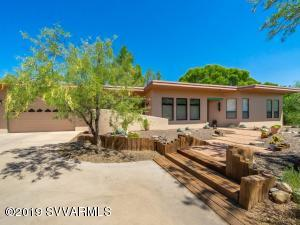 Truly a One-Of-A-Kind offering! Privacy, views, acreage, and a nice mix of desert meeting with an Oasis. Contenmporary ranch home with passive solar design. 3 bedrooms, plus office/den (with separate entrance) 2 baths and more.. Lovely reclaimed oak flooring in kitchen, dining and hallway, sunken livingroom with cozy woodstove and tons of natural light. Upgraded to include SS appliances, newer HVAC, water heater, roof recoat, paint and more....in addition the back has a wrap-around covered patio with tongue and groove ceilings to soak in the greenbelt views of your very own  3 acre + park w/ pond and spring feed irrigation. Owner filed for 21.6 acre feet of water rights. Lovely fruit trees, Cottonwood trees, berries, and fenced-in garden. All this yet close to historic downtown Clarkdale