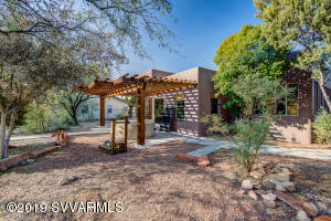 Open, airy and naturally bright Santa Fe style home with a serene, retreat style backyard is waiting for you! This newly renovated oasis has a decorative tile entryway and genuine wood floors throughout. The luxurious kitchen is spacious and opens up into the living room with a pellet stove and large retractable skylight! Great energy saving components! Beautiful french doors welcome you into the comforting backyard hosting a beautiful fountain shaded by mature trees. Fully fenced/walled backyard provide you with uninterrupted mountain views. Spa conveys and is waiting for you to relax in! Yard also offers RV sized carport and separately fenced portion, for your garden or your pets. This customized home can be everything you want it to be, and more! Won't last long, set up a showing today!