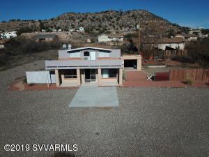 Rimrock, Turn those dreams into reality with a business downstairs and live upstairs or rent out one or both. Downstairs has 1500sqft commercial space with attached garage, storage, kitchen and 2 bathrooms, 1 is ADA compliant. Upstairs is a 2 bedroom 1 bath 1100sqft unit with ample storage, a laundry room and bonus room that could be used as an office or another bedroom. Living room has wood-burning fireplace, cozy dining area and kitchen has plenty of cabinets and smooth cooktop range. Lots of yard space for outdoor seating. Additional buildings may be added, if desired contact Yavapai County P&Z. Close to Montezuma's Well and in growing community by the school. This property has ADA parking, 2 septic tanks and its own well. Could be completely off grid with added solar panels.