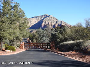 Framing Sedona's dramatic Red Rock formations on 1.29 acre. Ridge top home. Two complete living areas independent of each other. 2,384 sq. ft. GUEST LEVEL has private exterior entry, and a lockable entry from the home's first floor and guest level garage. Red Rock views, private patios, tall windows, sound system, kitchen/great room, 2 bathrooms, bedroom suite, private sitting room. MAIN LEVEL is 2,596 sq.ft.. and features a great room, 3 bedroom suites, private office, bonus room off of master suite. Kitchen has Wolfe & Subzero appliances, mesquite cabinets, granite & stone finishes. efficient laundry room. 2 bay garage. Heated pool with automatic cover. Rock walls, pavers, Low maintenance landscape. Wonderful home with many living options, dark skies, amazing panoramic views.