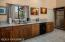 Hammered copper sink with brushed faucet; cedar cabinetry. Wall of pantry cabinets. Upgraded Granite counters.
