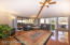 Vaulted ceiling with nice large beams for an architectural touch. Well lit with huge windows & custom window treatments.