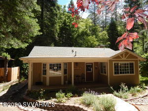 This great getaway tucked among the beautiful Pines in Oak Creek Canyon with the creek just behind the home. It is surrounded by beautiful gardens and mature landscaping. The cottage offers 1174 sq ft of living space and includes 2 beds and 2 full baths. Inside has been beautifully updated with stone counter tops, new cabinetry throughout, wood floors and a great wood burning stone fireplace for those cool nights. Outback the deck is surrounded by tall trees that offer plenty of shade and a path that leads to the creek.