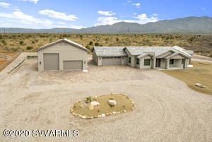 This CUSTOM NEW BUILD and Mid-Century Modern home is the definition of luxury and privacy. Enjoy gorgeous views of the Red Rocks and Mingus Mountain on your 2 acre Estate!!! Upon entrance you will find a custom electric steel gate with a complimenting portrait of the Mingus Mountain. With a 6-car garage AND RV Garage, you will have plenty of room for all of your toys! RV Garage features private living quarters and plenty of storage. In the guest quarters your guests will be treated with a fully equipped kitchen, custom tiled shower, laundry room, and separate bedroom. In the main home you will find high-end custom touches throughout. Kitchen features quartz countertops, brand new stainless steel KitchenAid Appliances