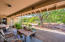 Covered patio with lush backyard living.