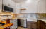 Schuler Cabinetry and floating shelves with leathered granite countertops and backsplash.