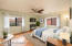 Spacious owner bedroom with fresh paint & the same beautiful flooring found in the home. Stay cool with the ceiling fan as you look out the front window to red rock views (partial virtual staging)