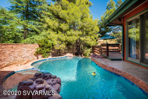 This 3,100 Square foot meticulously maintained home is filled with natural light, has excellent red rock views, and a gorgeous pool/hot tub with a waterfall feature! With a renovated kitchen AND a FABULOUS renovated in-law suite, this house has it all, including a beautiful, 1/2 acre parcel. Located in the thriving Village, 305 Conco Drive is close to shopping, banking, grocery, and many celebrated Sedona restaurants. Architectural detail, lots of gleaming glass windows with a view. Contemporary vaulted ceilings, this house has is ALL. The main level of the home has the owners suite with its own pool access. There are also two guest bedrooms (one of those bedrooms make a great office!) There are three enclosed walk-out patios on the main level of the home. Head downstairs via the