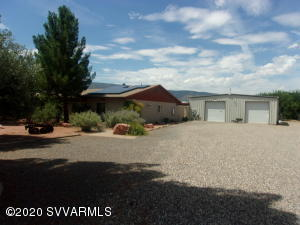 CAMP VERDE, 2,000sqft home, 2,400sqft garage with guest home on 1.25 acres. Large kitchen with plenty of cabinets and counter space, large gas range and island. Utility room has counters and cabinets. Master bedroom is open with a large picture window for the view, a gas fireplace and a door to covered patio. Walk-in closet has plenty of space, extra deep jetted tub and custom tiled walk-in shower. Guest rooms are spacious and have ceiling fans. Home has wood beamed ceiling Guest studio has sauna and a walk-in tiled shower, small sink in main room and skylight and several windows for added light. The garage/shop has bath with walk-in shower, full kitchen and an 8x16 freezer/refrigerator. Two 10x10 roll-up doors. Landscaped front yard w/ walkways and views of the mountains from the patio.