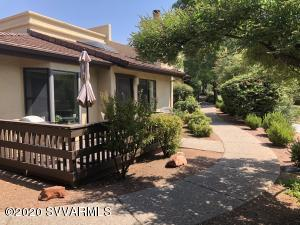Single level casita with open front deck and walled-in rear patio.