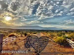 This is an opportunity to own 50 Acres with a 2,509sqft home w/ views of Mingus Mountain, Oak Creek and the Red Rocks of Sedona (they are spectacular!) The home sits high on a hill with a large patio overlooking the stunning 47.50 acres being sold with the home.  This house has a lot of storage, walk in closet, large hall closets, abundant pantry in kitchen, extra canning pantry & utility room. The land boasts expansive creek frontage w/ giant cottonwood trees, migrating birds, trout, deer, elk & easy creek access. This could be a developers dream with 4 wells existing, 2 septic tanks, private gated entrance, power and roads all in place. Or make it your own family compound, vineyard or build your dream home! The possibilities are endless. This is a rare opportunity and it wont last long!